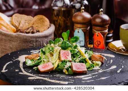 Seared tuna coated sesame seeds with green salad on black stone plate - stock photo