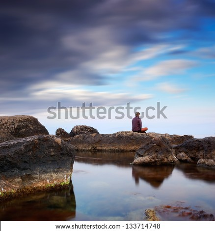 Seascape. A guy is sitting on a rock by the sea and looks into the distance - stock photo