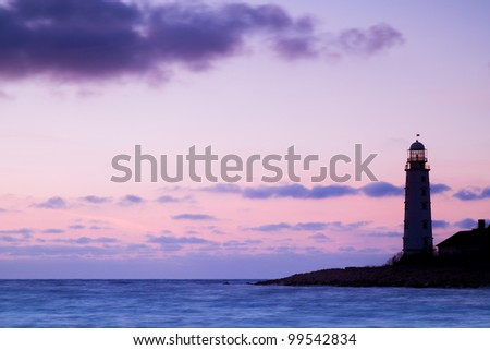 Seascape at sunset and the lighthouse on the coast