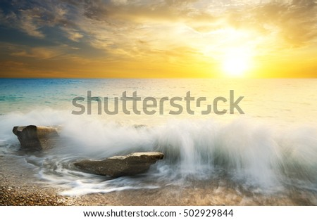 seascape at sunset.descending over the horizon the bright sun illuminating a sea of stormy waves and clouds at sunset.sea waves breaking on rocks on the beach.