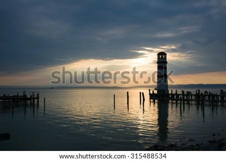Seascape at sunset. Lighthouse on the coast. - stock photo