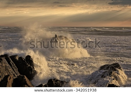 Seascape at sunset with stormy waves breaking over cliffs and rocks against an enhanced dramatic sky with sunbeams - stock photo