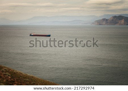 Seascape. Cargo ship in the sea on the background of the coast - stock photo