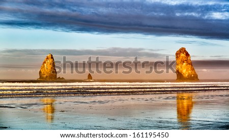 Seascape featuring sea stack rock formations lit dramatically at dawn. Location: Cannon Beach, Oregon, USA in the Pacific Northwest - stock photo