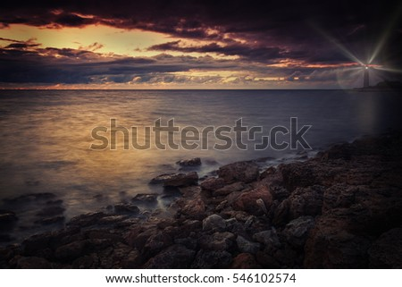 Seascape.Lighthouse on the seashore at night with rays of light