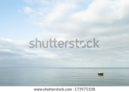 Seascape. Lonely boat on a quiet sea surface - stock photo