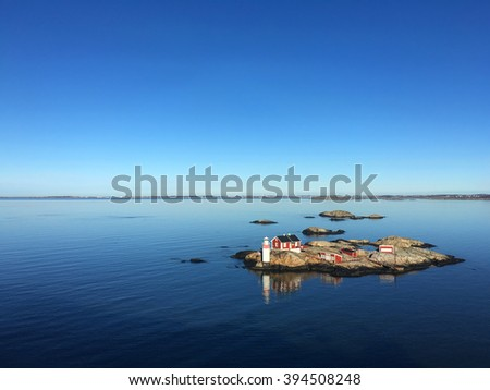 seascape of a swedish fjord with a red house and a little lighthouse on a rocky island - stock photo