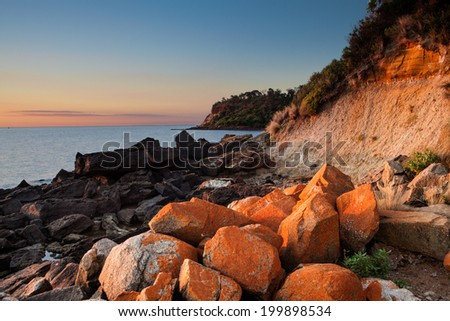 Seascape of Sunset with orange rocks on foreground - stock photo