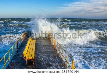 seascape on a stormy sunny day with big waves breaking at a pier and a yellow bench