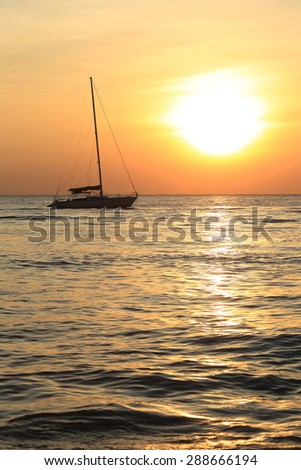 seascape scenic sunset and anchored boat with deflated sails off the coast of Thailand