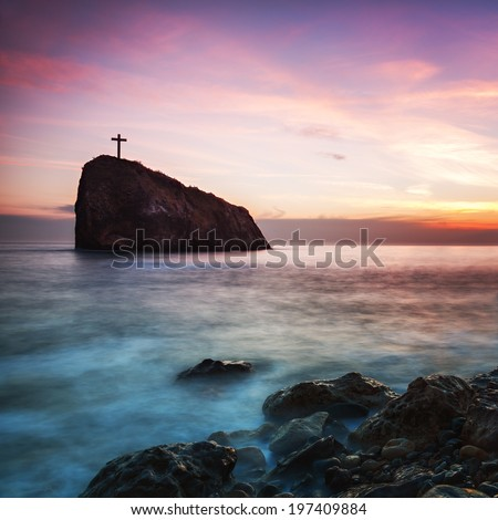 Seascape. Seacoast at sunset and a cross on a rock - stock photo