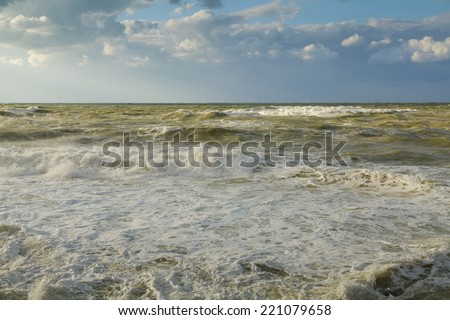 Seascape. Storm in ocean with big windy waves. Nature composition on a background blue sky with white clouds.