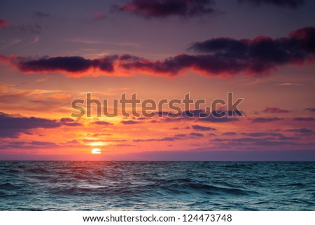 Seascape. Sun in the clouds at sunset over the sea - stock photo