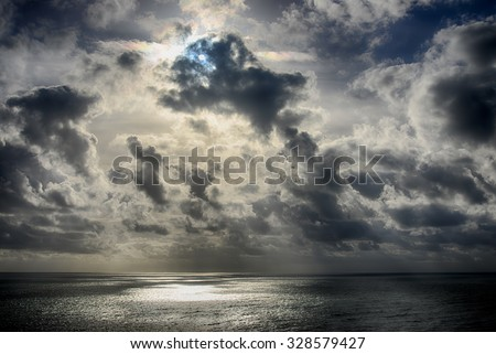Seascape-Sun rays shining through the clouds and reflected in the sea.HDR image