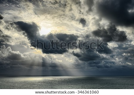 Seascape-Sunbeams shine through the clouds and reflected in the sea.HDR image - stock photo