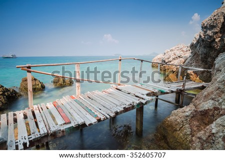 Seascape view with wooden walkway and brown rocks