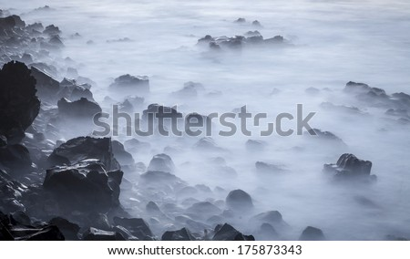 Seascape, waves in a long exposure, sea and rocks in the evening,