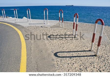 Seascape with a ship and pier with metal fence - stock photo