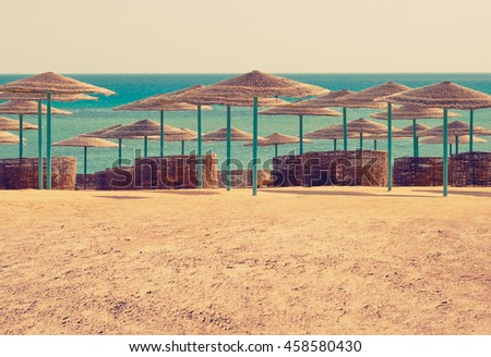 Seascape with beach umbrellas on sand beach. Sea vacation on a resort in summertime. Straw sunshades for tourists on tropical island - travel concept background for summer leisure. - stock photo