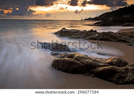 Seascape with motion wave at sunset in Kalim beach, Phuket, Thailand - stock photo