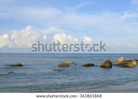 seascape with picturesque blue clouds sky above stones in water at seashore - stock photo