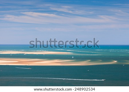 Seascape with sandbanks, yachts and boats - stock photo