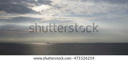 Seascape with ships on the horizon and cloudy sky