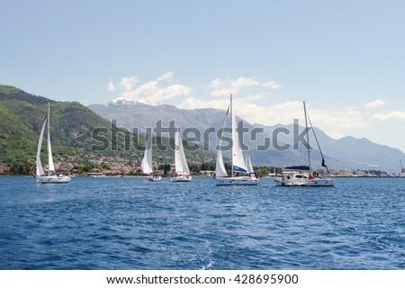 "Seascape with yachts. Tivat, Montenegro - 26 April, 2016. Regatta ""Russian stream"" in God-Katorskaya bay of the Adriatic Sea off the coast of Montenegro. - stock photo"