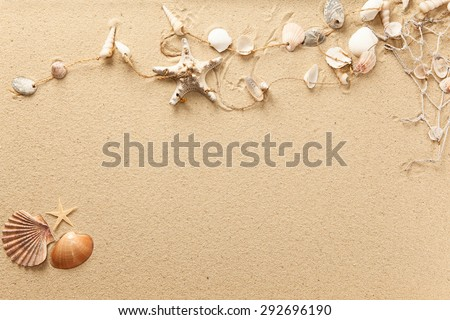 Seashells and net on the beach with room for text - stock photo