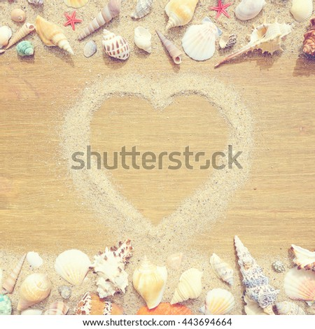 Seashells and starfish on a old wooden background. Silhouette of the heart made of sand. Photo in vintage style - stock photo