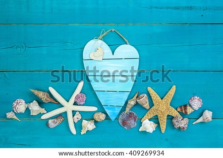 Seashells and starfish on antique rustic teal blue wood background; blank broken heart beach sign with hearts - stock photo