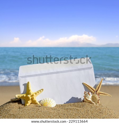 Seashells and starfish with open envelope with blank letter on sand beach - stock photo