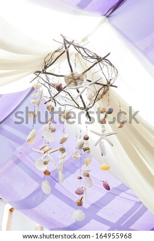 Seashells Mobile with white curtain on tropical resort - stock photo
