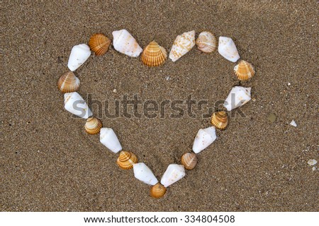 Seashells on the beach lined in shape of heart - stock photo