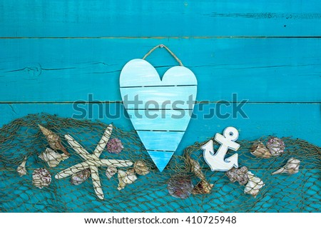 Seashells, starfish, anchor and fish net border on antique rustic teal blue wood background; blank nautical sign - stock photo