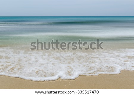 Seashore and smooth waves with sharp focus in foreground - stock photo