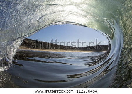 Seashore framed by a curling wave - stock photo