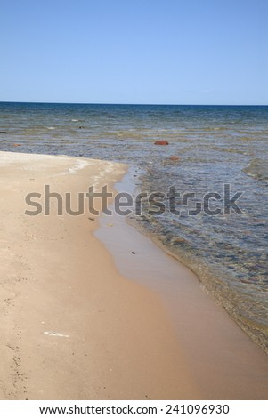 Seashore - Lake Huron. Waves reach long rocky shoreline beach of Great Lakes in Michigan - stock photo