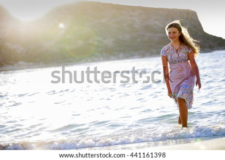 Seashore sunset walk, young girl on the beach - stock photo