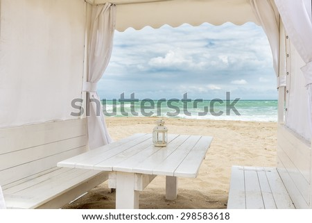 Seashore view through a white tent with table facing the sea - stock photo