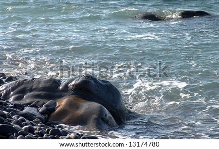 Seashore with stones during surf. Photography.