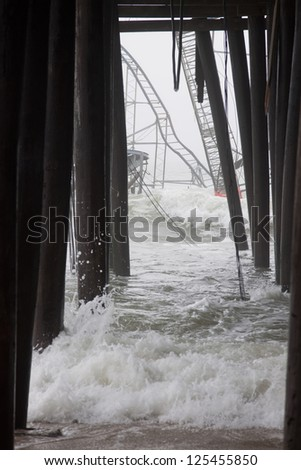 SEASIDE HEIGHTS, NJ - JAN 13: Waves break against the submerged Casino Pier Star Jet roller coaster and pilings on January 13, 2013 in Seaside Heights, NJ. Hurricane Sandy made landfall 75 days ago. - stock photo