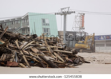 SEASIDE HEIGHTS, NJ - JAN 13: Wooden planks piled up on the beach on January 13, 2013 in Seaside Heights, New Jersey. Clean up continues 75 days after Hurricane Sandy struck the shore in October 2012. - stock photo