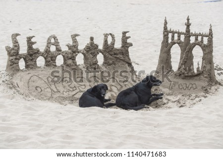 Seaside, OR / USA - July 22 2018: Sand castle on the beach with words Seaside and Oregon fun on it. Two dogs lay in the hole near the sculpture.