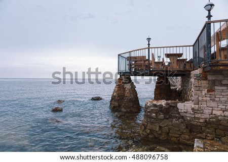 Seaside restaurant terrace in Croatia on stone pillars with view of the horizon