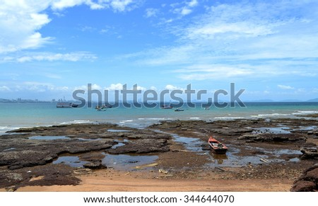 Seaside rock crevices Fishing boats returning to shore in the morning blue sky . - stock photo