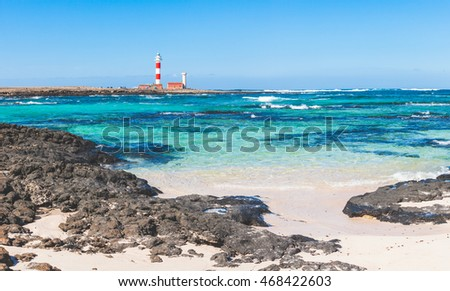 Seaside view in Fuerteventura with clear water and lighthouse on background. There are some black rocks on foreground and underwater. Summer and travel concepts.