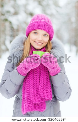 season, christmas, drinks and people concept - happy smiling young woman with cup drinking hot tea in winter forest