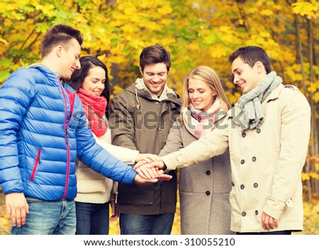 season, friendship, gesture and people concept - group of smiling men and women with hands on top in autumn park
