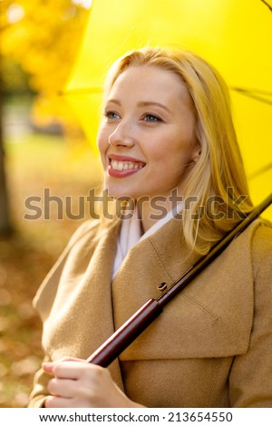 season, happiness and people concept - smiling woman with umbrella in autumn park - stock photo